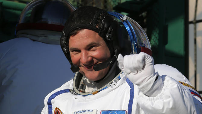 Russian cosmonaut Roman Romanenko, crew member of the mission to the International Space Station, gestures prior the launch of the Soyuz-FG rocket at the Russian leased Baikonur cosmodrome, Kazakhstan, Wednesday, Dec. 19, 2012. (AP Photo/Dmitry Lovetsky, Pool)