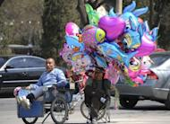 A migrant couple sell balloons on a street in Beijing on April 12, 2012. A new World Bank report projects GDP growth in China will be 8.2 percent in 2012 and 8.6 percent in 2013