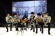 Donika Sterling from New York, third left, talks with members of South Korean pop group SHINee in Seoul, South Korea, Wednesday, June 20, 2012. The 15 year-old American K-pop fan, who is suffering a disease that gradually causes loss of muscle tissue and slows down parts of the body, met and sang with the boy band she idolizes. (AP Photo/Lee Jin-man)