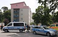 Police stand in front of the house where a gunman had taken several people hostage in Karlsruhe, southwestern Germany. A police spokesman said the hostage-taker and all his hostages were dead after he barricaded himself and them into an apartment block