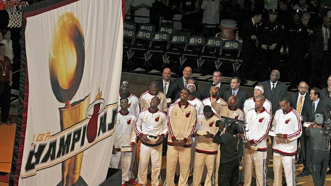 Miami Heat players and coaches watch as the 2013 NBA championship banner is raised before the Heat's season-opener basketball game against the Chicago Bulls on Tuesday, Oct. 29, 2013, in Miami