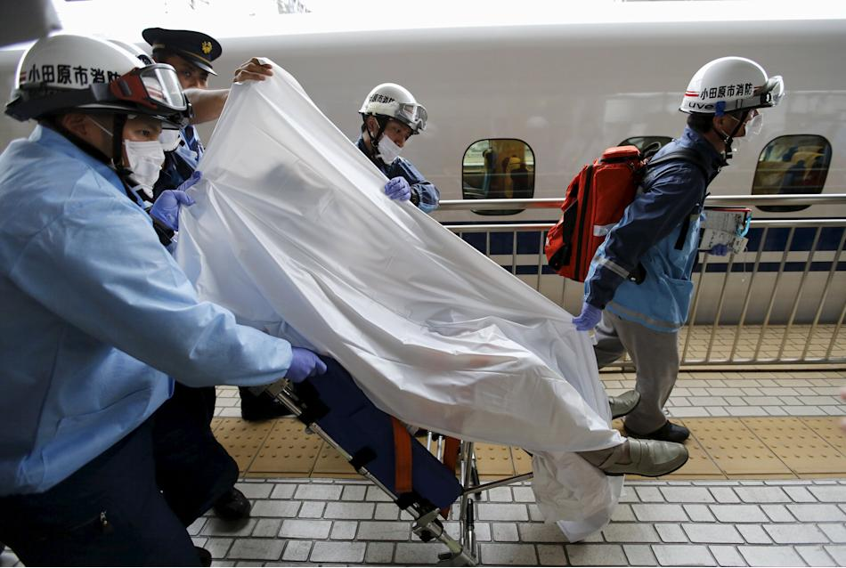 A passenger on a stretcher is carried by ambulance officers as the passenger gets off a Shinkansen bullet train at Odawara station after it made an emergency stop, in Odawara, west of Tokyo