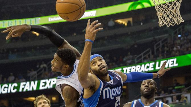 Dallas Mavericks' Vince Carter (25) and Orlando Magic's Solomon Jones, left, fight for the ball during the first half of an NBA basketball game in Orlando, Fla., Saturday, Nov. 16, 2013