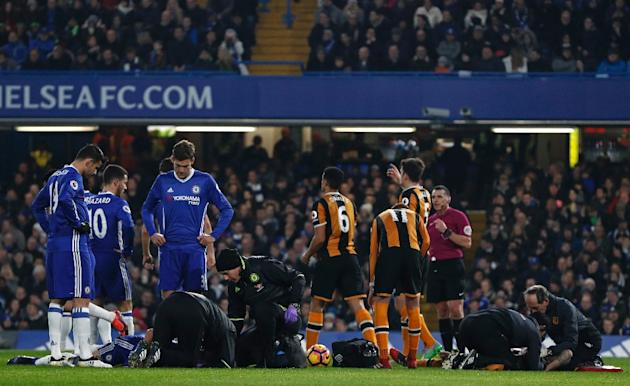 Chelsea defender Gary Cahill and Hull City midfielder Ryan Mason receive medical treatment after a clash of heads during the English Premier League match at Stamford Bridge in London on January 22, 20