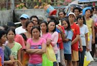 People affected by a powerful earthquake in February queue up to receive relief goods in Guihulngan town in central Philippines on February 9. Residents on the Philippines' Pacific coast have described how they ran for their lives when a major offshore earthquake triggered a tsunami warning this week, as thousands returned home