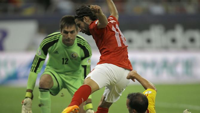 Turkey's Olcay Sahan, center, challenges Romania's Vlad Chiriches for the ball as goalkeeper Ciprian Tatarusanu, left, tries to block him during a World Cup Group D qualifying soccer match between Romania and Turkey at the National Arena stadium in Bucharest, Romania, Tuesday, Sept. 10, 2013