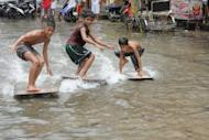 Children use plywood to surf in a flooded street in Navotas in suburban Manila in August. Typhoon Bopha, expected to hit the southern island of Mindanao overnight, is the strongest typhoon to hit the Philippines this year.