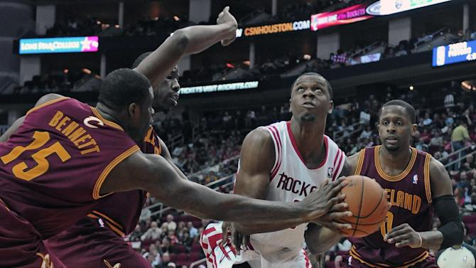 Houston Rockets' Terrence Jones, in white, is surrounded by Cleveland Cavaliers Anthony Bennett (15), Henry Sims and C.J. Miles (0) in the second half of an NBA basketball game Saturday, Feb. 1, 2014, in Houston. The Rockets won 106-92