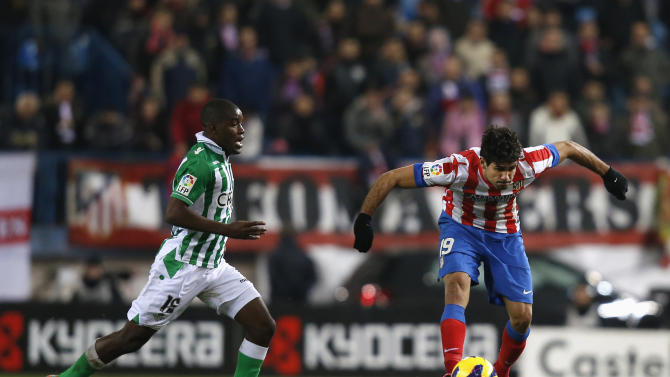 Atletico Madrid's Costa controls the ball next to Real Betis' Joel during their Spanish first division soccer match at Vicente Calderon stadium in Madrid