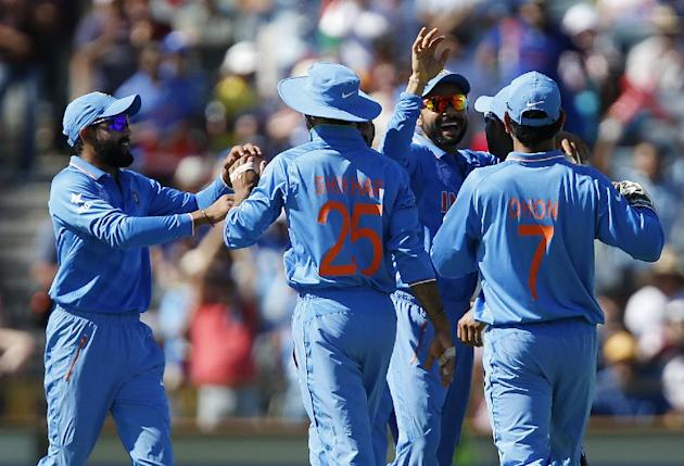 Indian players congratulate teammate Virat Kohli, second right, after he ran out West Indies batsman Marlon Samuels during their Cricket World Cup Pool B match in Perth, Australia, Friday, March 6, 20