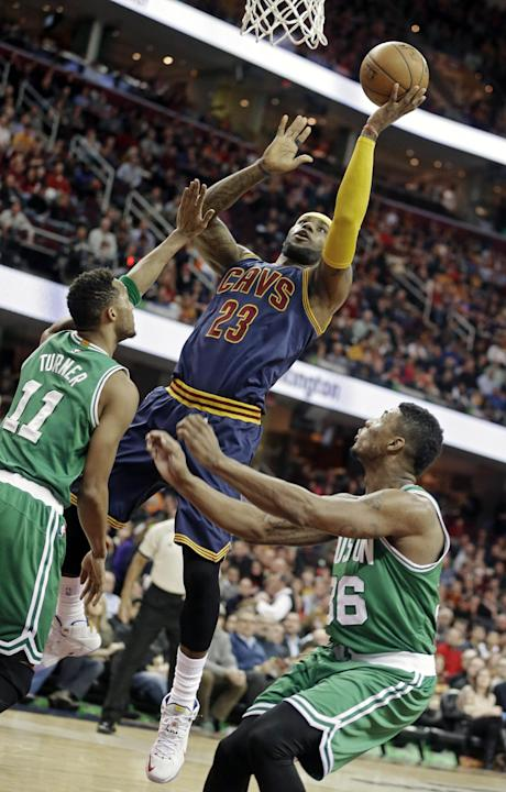 Cleveland Cavaliers' LeBron James (23) shoots against Boston Celtics' Evan Turner (11) and Marcus Smart (36) in the first quarter of an NBA basketball game Tuesday, March 3, 2015, in Cleveland