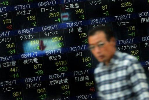 A man walks past a board displaying share prices for the Tokyo Stock Exchange in front of a securities company in Tokyo in October 2012. Tokyo stocks opened 0.41 percent lower on Tuesday after overnight drops on Wall Street following poor manufacturing data.