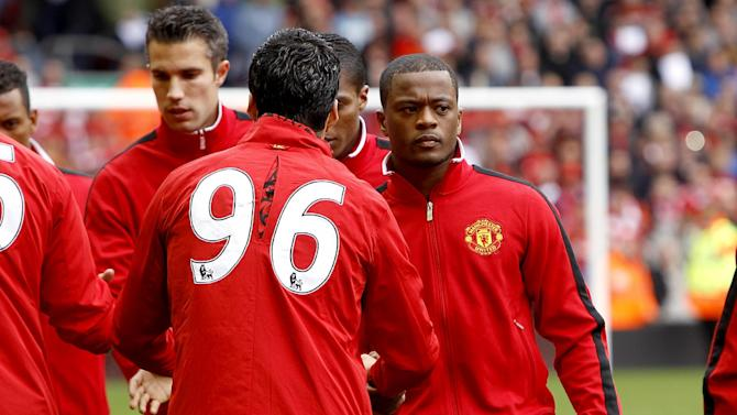 Liverpool's Luis Suarez, left, and Manchester United's Patrice Evra shake hands prior to kick-off
