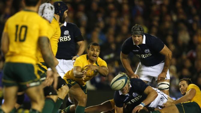 Australia's Will Genia passes to Quade Cooper during their rugby union international test match against Scotland at Murrayfield Stadium in Edinburgh
