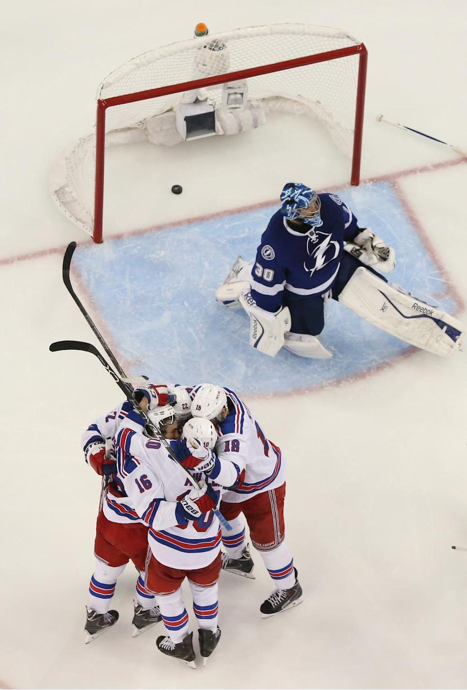 New York Rangers surround center J.T. Miller (10) after he scored against Tampa Bay Lightning goalie Ben Bishop (30) during the third period of Game 6 of the Eastern Conference finals in the NHL hocke