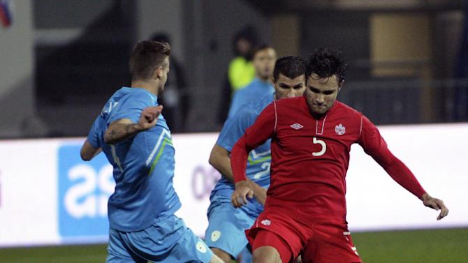 Canada's Adam Straith, right, is challenged by Slovenia's Miral Samardzic during a friendly soccer match between Slovenia and Canada, in Celje, Slovenia, Tuesday, Nov. 19, 2013