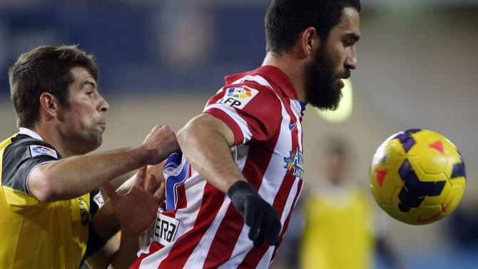 """Atletico Madrid's Arda Turan fights for the ball with Sevilla's Jorge Andujar Moreno """"Coke"""" during their Spanish First Division soccer match at Vicente Calderon stadium in Madrid"""