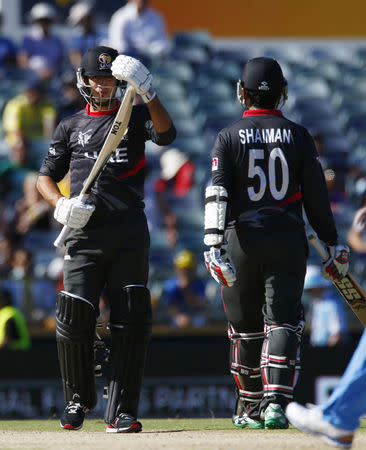 UAE's Rohan Mustafa walks off the pitch past his team mate Shaiman Anwar after being dismissed LBW off the bowling of India's bowler Mohit Sharma during their Cricket World Cup match in Perth