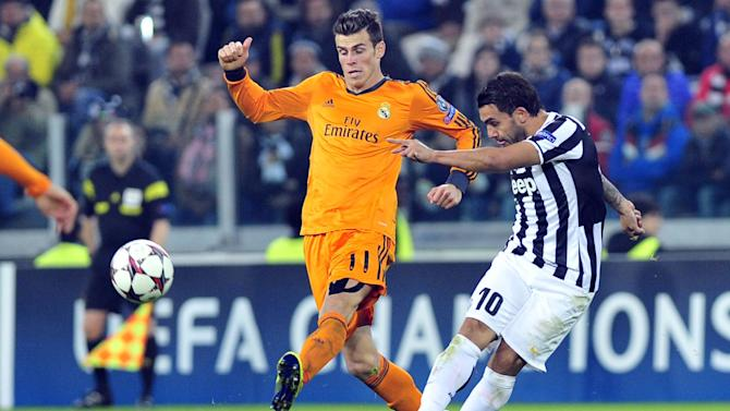 Juventus forward Carlos Tevez, right, of Argentina, challenges for the ball with Real Madrid midfielder Gareth Bale during the Champions League, Group B, soccer match between Juventus and Real Madrid at the Juventus stadium, in Turin, Italy, Tuesday, Nov. 5, 2013