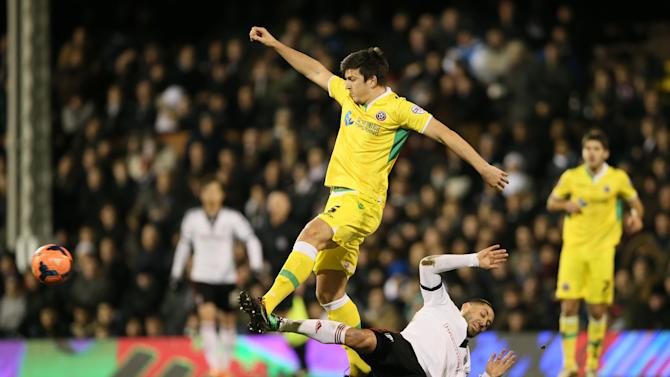 Fulham's Clint Dempsey, falls to the ground as he challenges Sheffield United's Harry Maguire for the ball during their 4th round replay English FA Cup soccer match between Fulham and Sheffield United at Craven Cottage stadium in London, Tuesday, Feb. 4, 2014. (AP Photo/Alastair Grant)