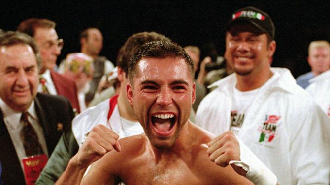 In this June 7, 1996 file photo, newly crowned WBC super lightweight champion Oscar De La Hoya poses with the belt he won from Julio Cesar Chavez by TKO in the fourth round in Las Vegas. De La Hoya, Felix Trinidad and Joe Calzaghe head the class of 2014 to be inducted into the International Boxing Hall of Fame