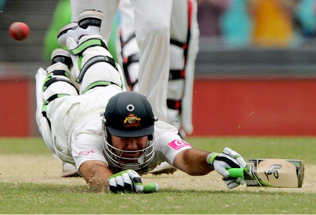 Australian batsman Ricky Ponting dives to make his ground and score a run to reach his 100 on day two of the second cricket test against India at the Sydney Cricket Ground on January 4, 2012. RESTRICT