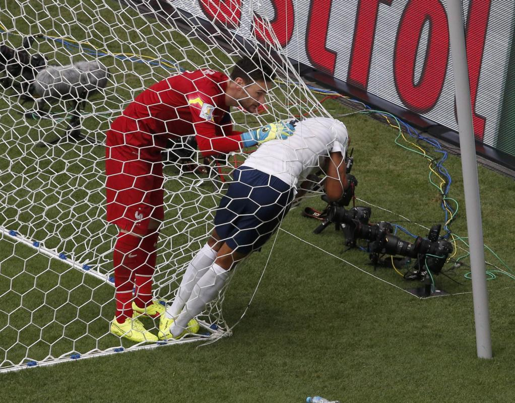 France's Varane stands in the net after being hit in the face by a ball during their 2014 World Cup round of 16 game against Nigeria in Brasilia