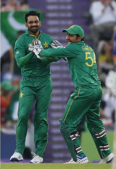 Pakistan's Mohamed Hafeez (L) celebrates the wicket of England's Alex Hales with Sarfraz Ahmed