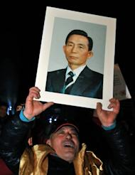 A supporter of Park Geun-Hye is pictured holding a portrait of her father Park Chung-Hee on December 20, 2012. Park Chung-Hee ruled South Korea with an iron fist for 18 years until his eventual assassination, and remains a divisive figure.