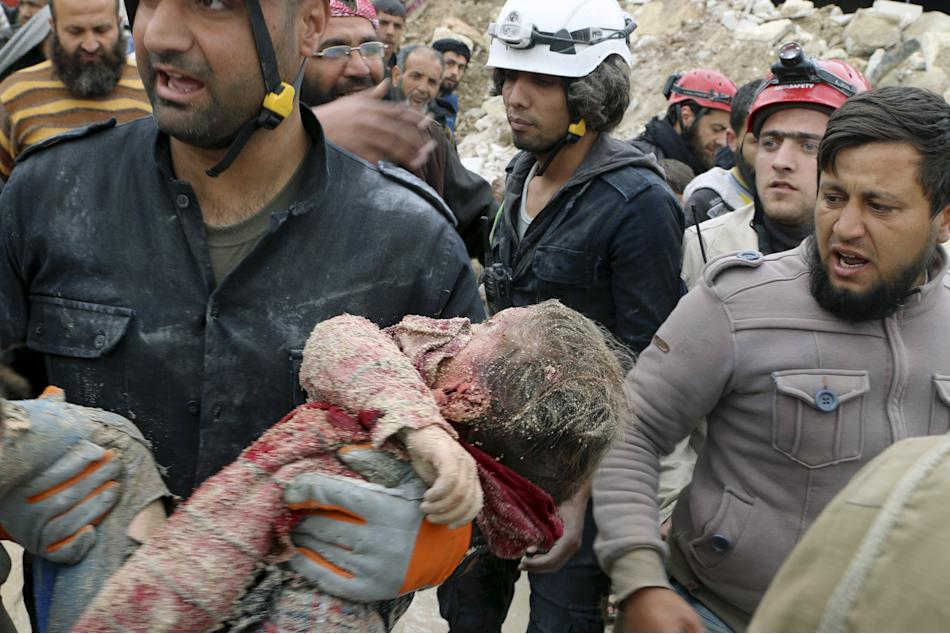 Civil defence members carry a dead child after what activists said was shelling by warplanes loyal to Syria's president Bashar Al-Assad in Aleppo's rebel-controlled Bab Al-Nairab district