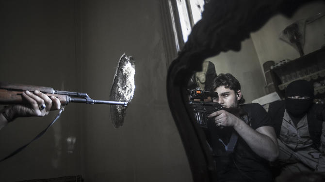 FILE - A rebel sniper aims at a Syrian army position, seen with another rebel fighter reflected in a mirror, in a residential building in the Jedida district of Aleppo, Syria on Monday, Oct. 29, 2012. (AP Photo/Narciso Contreras, File)