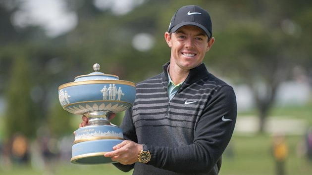 Rory McIlroy poses for photos with the Walter Hagen trophy.