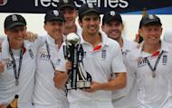 England's Alastair Cook (C) holds the trophy with teammates as England celebrates a series win on the fifth day in the second international cricket Test match between England and New Zealand at Headingly in Leeds on May 28, 2013. Graeme Swann bowled England to a commanding 247-run in the second Test against New Zealand in Leeds on Tuesday with rain unable to save the tourists
