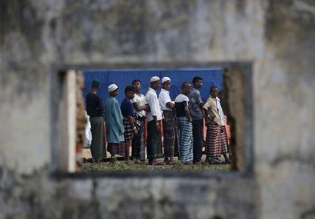 Rohingya migrants who arrived in Indonesia last week by boat are seen through the window of an abandoned building as they wait in line for breakfast at a temporary shelter in Aceh Timur regency near L
