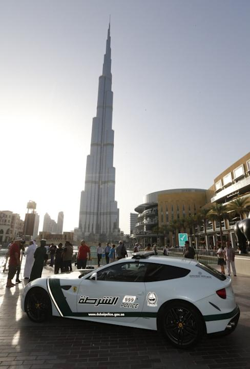 A picture taken on April 25, 2013 shows a Ferrari police vehicle in front of the Burj Khalifa tower in the Gulf emirate of Dubai. Two weeks after introducing the Lamborghini police car, Dubai Police h