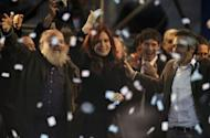 Argentine President Cristina Fernandez de Kirchner (C) waves to the crowd during a political gathering to commemorate the ninth anniversary of the election that took her late husband, former president Nestor Kirchner, to power in 2003, at Velez Sarsfield's football stadium in Buenos Aires, on April 27