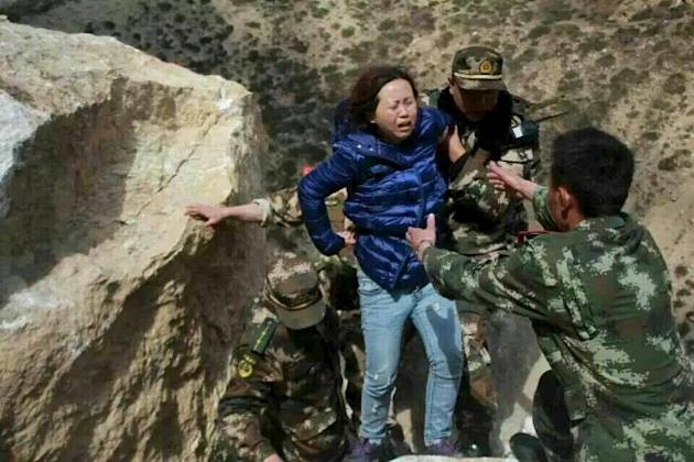 Rescuers help a woman to get to safe area after a landslide, after a 7.9 magnitude earthquake hit Nepal, in Xigaze Prefecture