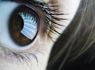 "A binary code is reflected from a computer screen in a woman's eye on October 22, 2012. The British military's dependence on information technology means it could be ""fatally compromised"" by a cyber-attack but the government seems unprepared for such an event, lawmakers warned Wednesday"