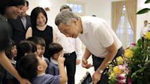Singapore Prime Minister Lee Hsien Loong speaks to a pre-school student who told him that his father, the late Lee Kuan Yew, has gone to heaven, during a private family wake at the Istana, or Presidential Palace, Tuesday, March 24, 2015, in Singapore. Singapore mourned longtime leader Lee with raw emotion and a blanket of relentlessly positive coverage on its tightly scripted state television on Monday, mythologizing a man who was as respected as he was feared. (AP Photo/Wong Maye-E)