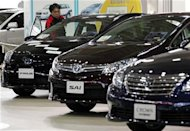 A staff of Toyota Motor Corp checks the inside of a vehicle displayed at the company's showroom in Tokyo
