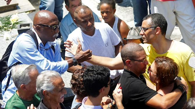 Alexandre Torres, son of the late former Brazilian soccer captain Carlos Alberto Torres, is greeted by former player Paulo Cesar at the Iraja cemetery for burial in Rio de Janeiro