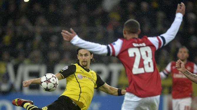 Dortmund's Neven Subotic, left, shoots against Arsenal's Kieran Gibbs during the Champions League group F soccer match between Borussia Dortmund and Arsenal FC in Dortmund, Germany, Wednesday, Nov. 6, 2013