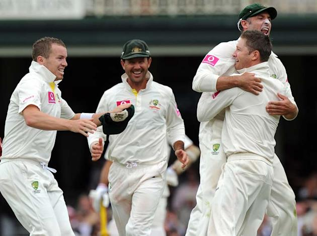 After catching legendary Indian batsmen Sachin Tendulkar for 80 at first slip, Mike Hussey (R) leaps into the arms of Australian captain and bowler Michael Clarke (2nd R) as teammates Peter Siddle (L)