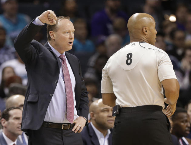 Atlanta Hawks head coach Mike Budenholzer, left, argues a call with referee Marc Davis, right, during the first half of an NBA basketball game against the Charlotte Hornets in Charlotte, N.C., Saturda