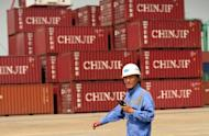 "A worker walks through Shanghai Container Port in Baoshan district of Shanghai on July 10, 2012. Chinese leaders have vowed to take further measures to boost the slowing economy. Premier Wen Jiabao this week called stabilising economic growth the government's ""top priority"""