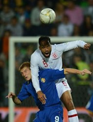 Lescott Joleon (R) of England jumps for the ball with Piscusciac Igor of Moldova during their World Cup 2014 qualifier football match in Chisinau city. England won 5-0