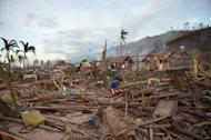 Residents pick through their destroyed homes in the aftermath of Typhoon Bopha at a village in Boston town, Davao Oriental. The death toll from the strongest typhoon to hit the Philippines this year has climbed above 700 with hundreds more missing