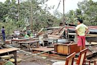 A man looks at his damaged house destroyed by Typhoon Bopha in Butuan City, Agusan del Norte, in the southern Philippine island of Mindanao. Officials said many of the Mindanao victims were poor migrants who have flocked by the thousands to mountainous, landslide-prone sites like the towns of New Bataan and Monkayo to work at unregulated, small-scale gold mines