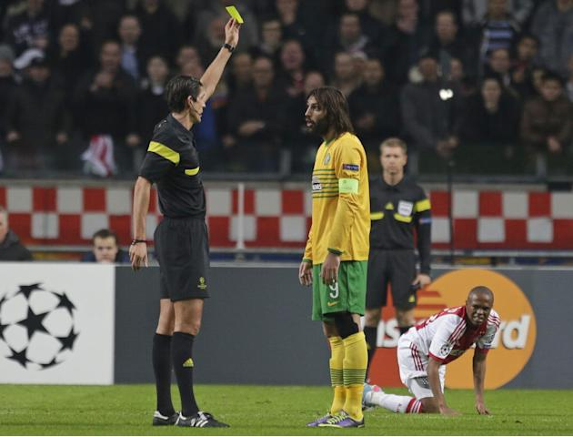 Referee Deniz Aytekin of Germany shows a yellow card to Celtic's Giorgos Samaras, center, after he fouled Ajax's Thulani Serero, rear right, during the Champions League Group H soccer match between Aj