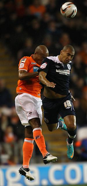 Alex Baptiste, left, challenges James Vaughan in the air during Huddersfield's victory